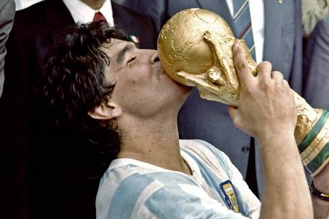 (FILES) In this file photo taken on June 29, 1986 Argentina's football star team captain Diego Maradona kisses the World Soccer Cup won by his team after a 3-2 victory over West Germany on at the Azteca stadium in Mexico City. - Argentine football legend Diego Maradona will be buried on November 26, 2020 on the outskirts of Buenos Aires, a spokesman said. Maradona, who died of a heart attack Wednesday at the age of 60, will be laid to rest in the Jardin de Paz cemetery, where his parents were also buried, Sebastian Sanchi told AFP. (Photo by - / AFP) ORG XMIT: DOC21
