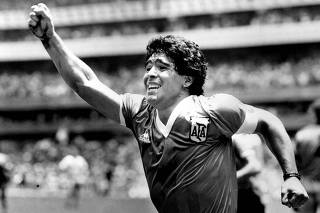 FILE PHOTO:  Argentinian star Diego Maradona raises his arm in the air after scoring