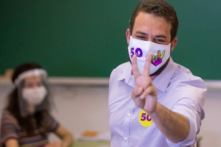 O candidato à prefeitura de São Paulo, Guilherme Boulos (PSOL), está de camisa e máscara com o número de sua legenda, 40. Ele posa para foto com fazendo a letra V com a mão esquerda. Atrás, uma mulher sentada, desfocada, e uma lousa escolar