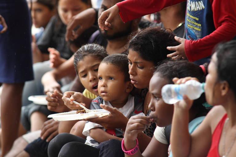 imigrantes estão juntos e comendo uma refeição