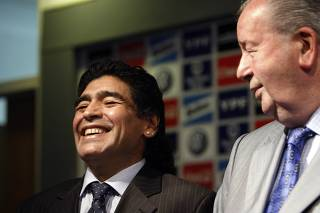 Argentine soccer great Maradona laughs next to Argentina Football Association President Grondona at the Argentine squad's camp on the outskirts of Buenos Aires