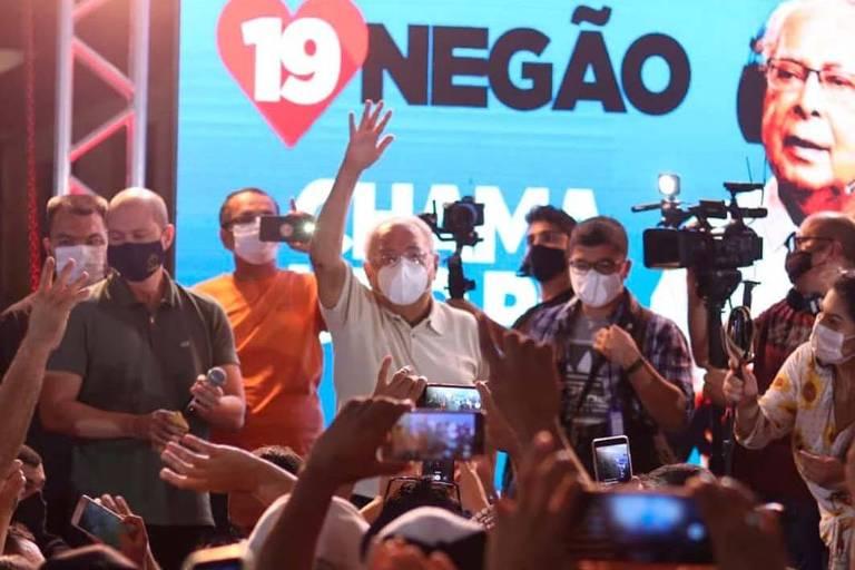 homem de máscara no palco fala para uma multidão