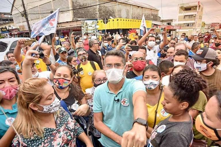 homem de máscara faz campanha de rua em meio a multidão