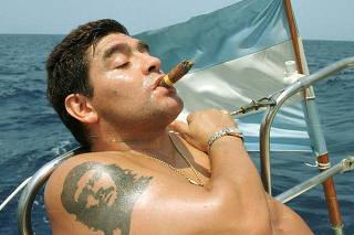 FILE PHOTO: Argentine soccer star Diego Maradona smokes a Cohiba as he rides a sailboat