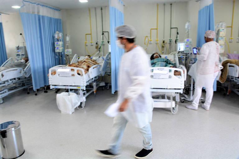 Homem de avental que parece ser um médico passa por ala de hospital com leitos ao fundo