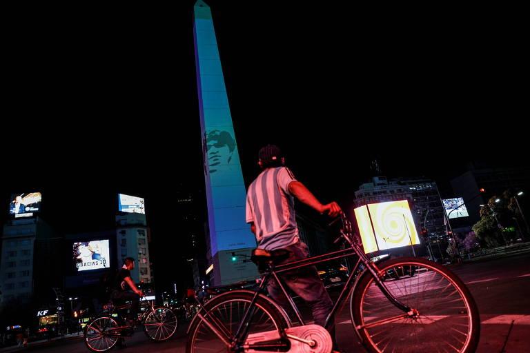 Ciclistas observam Obelisco com projeção do rosto de Maradona na noite desta quinta (26)