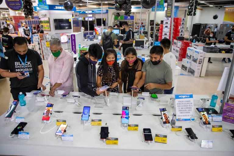 Consumidores de máscara olhando celulares em loja de eletrodomésticos