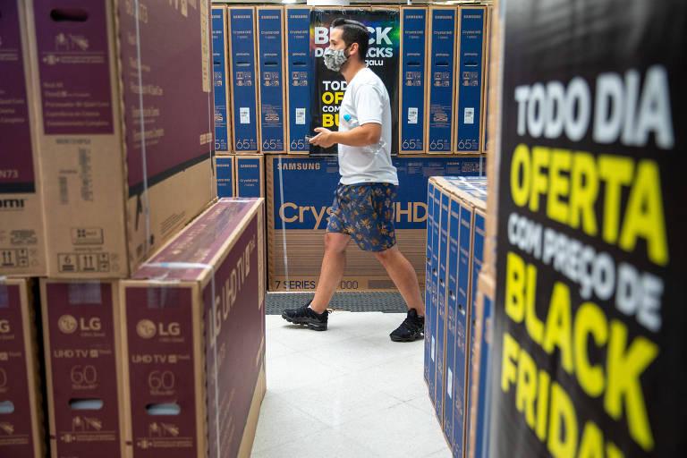 Um homem de mascara caminha entre pacotes de televisores empilhados