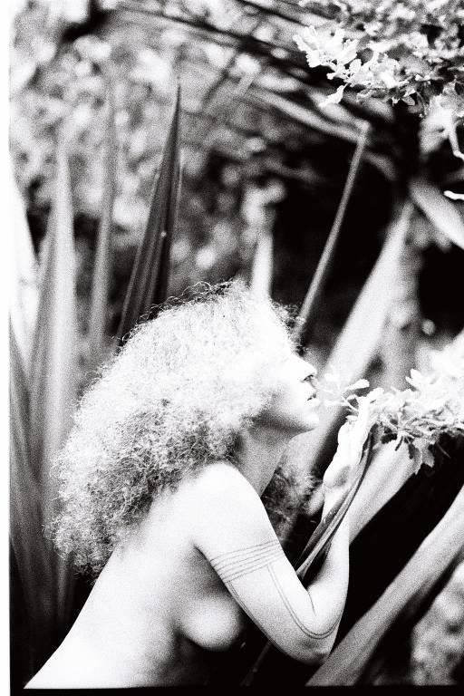 Mulher com seios de fora de lado e com seu cabelo armado em foto em preto e branco
