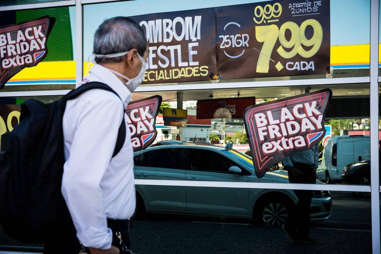 Homem veste roupa social e tem uma mochila nas costas; ele observar um vidro com cartazes de descontos do supermercado Extra