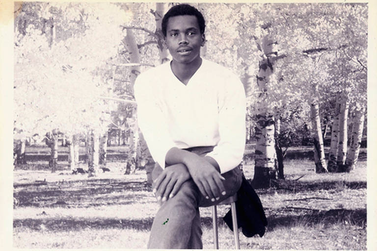 Homem negro sentado em foto preto e branco