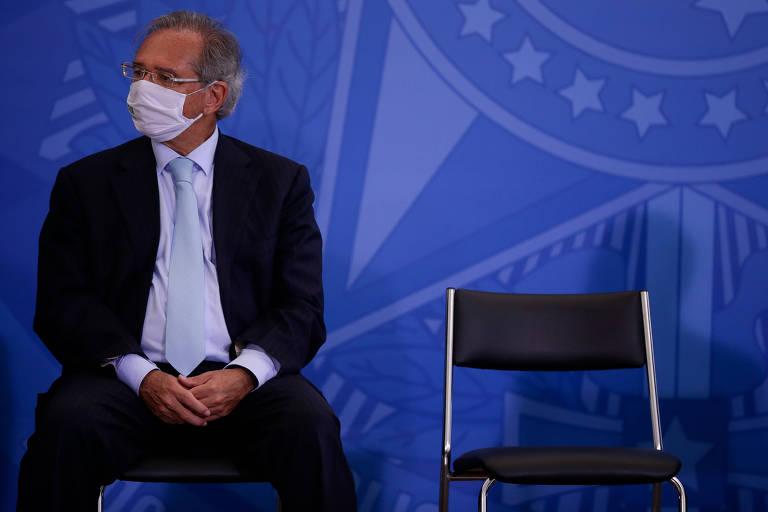 Paulo Guedes usa terno e máscara; ele está sentado ao lado de uma cadeira vazia