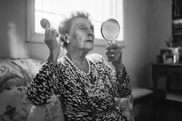 retrato em preto e branco de mulher idosa que penteia os cabelos segurando um pequeno espelho em uma das mãos
