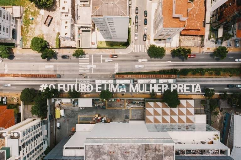 """vista aérea da frase  """"O futuro é uma mulher preta""""  inscrita no concreto"""