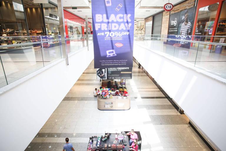 Banner roxo anuncia desconto de Black Friday em um shopping vazio