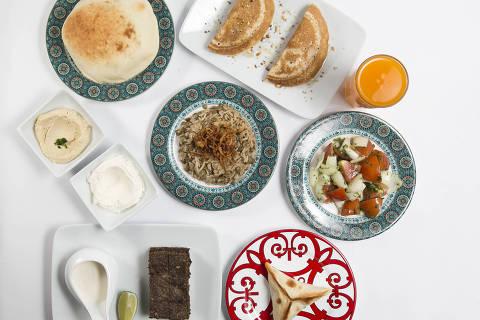 SAO PAULO, SP, BRASIL, 04-03-2015: Duas mil calorias da Cozinha Arabe representada em: 1pao sirio; coalhada seca; homos; esfira fechada de carne; salada arabe; arroz com lentilha; kibe assado; ataf nozes; e suco de tangerina. Refeicoes de ate 2.000 calorias (a quantidade recomendada para um dia todo), representadas em cinco cozinhas bem representativas de Sao Paulo; Italiana, Arabe, Japonesa, Brasileira e
