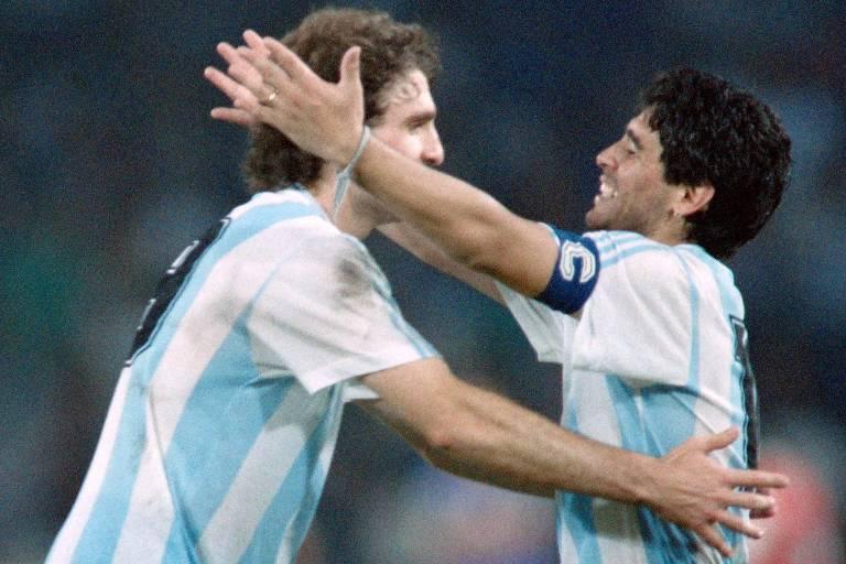 Oscar Ruggeri e Maradona se abraçam durante partida da seleção argentina na Copa do Mundo de 1990