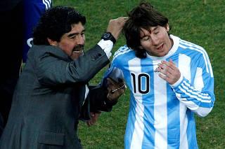 FILE PHOTO: Argentina's coach Diego Maradona celebrates with Argentina's Lionel Messi at Soccer City stadium