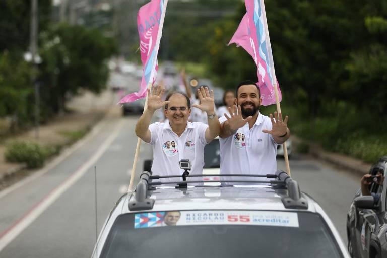 dois homens de camiseta branca faze carreata com bandeiras rosas atrás.