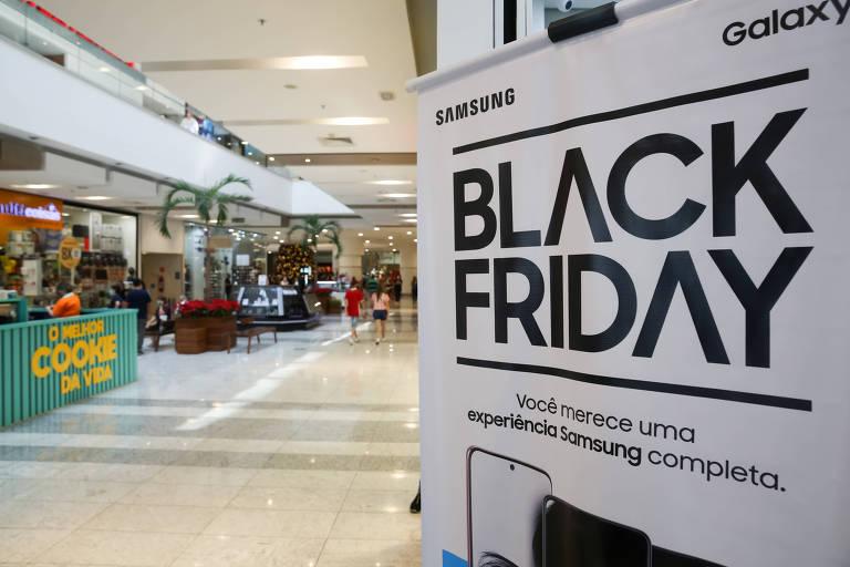 Cartaz anuncia a Black Friday em porta de loja de shopping que tem pouca movimentação