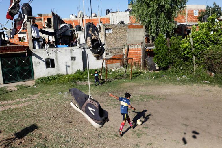 Crianças jogam futebol em um campinho improvisado da Villa Fiorito