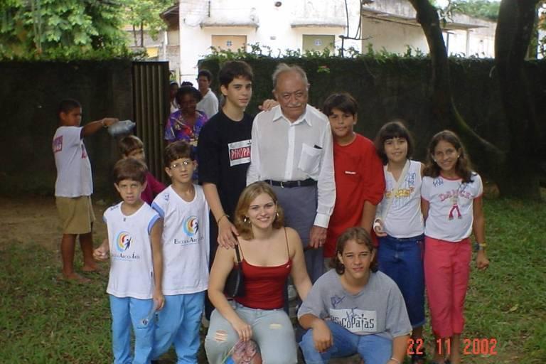 Em imagem de arquivo pessoal de 2002, João Campos (criança, de óculos), Marília Arraes (vermelho) e Miguel Arraes ao redor de crianças