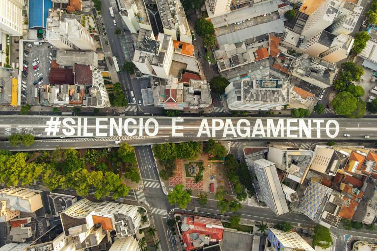 """vista aérea da frase """"silêncio é apagamento"""" escrita no viaduto de concreto que corta o bairro dividindo prédio e casas"""