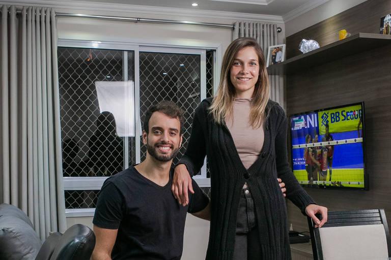 Homem sentado e mulher em pé posam sorridentes para a foto na sala de um apartamento