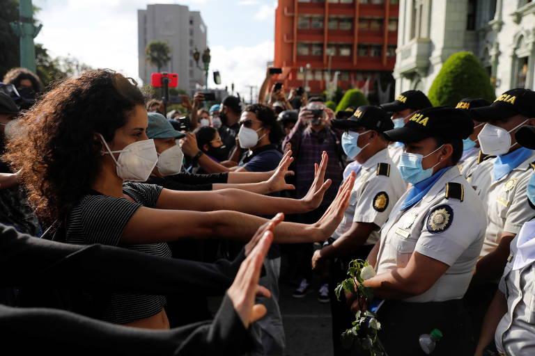 Manifestantes estendem os braços diante de barreira de policiais