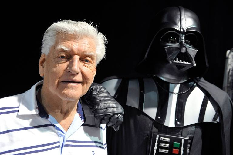 David Prowse ao lado da armadura de Darth Vader, personagem que interpretou, em 2013