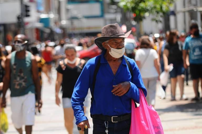 Homem de camisa azul e chapéu com sacola no braço usa máscara anticovid com o nariz para fora; ao fundo há muitas pessoas em um calçadão, parte com e parte sem máscara