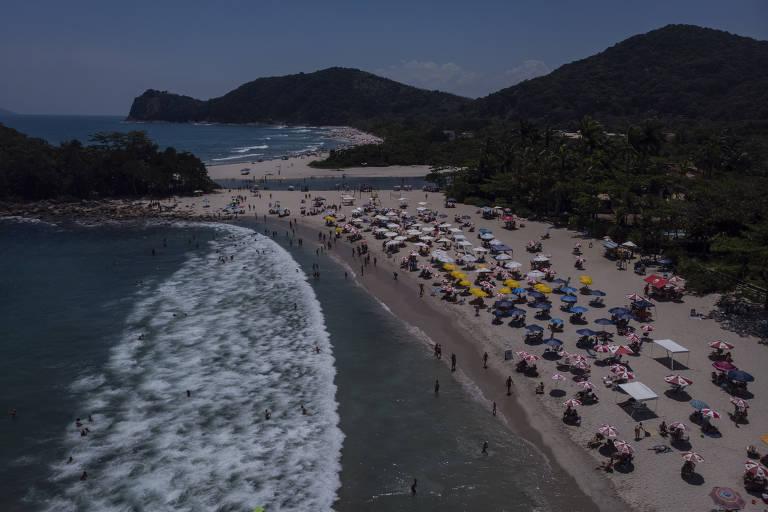 Mar e faixa de areia, vista aérea, pode-se ver dezenas de guarda-sóis com um pouco de distanciamento de um para o outro, praia não está vazia, mas também não está lotada, alguns banhistas estão no mar