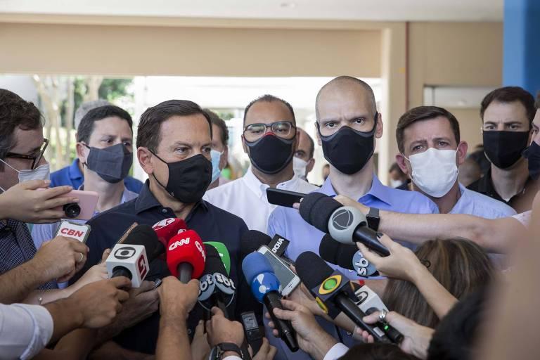 Microfones de repórteres se voltam a Doria, ao lado de Covas, após a votação do governador em SP
