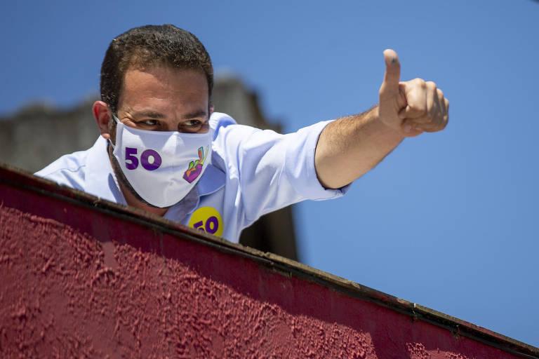 Guilherme Boulos, no dia do segundo turno da disputa à Prefeitura de São Paulo, aparece em uma sacada de cimento vermelho vinho. Ele está de máscara e faz sinal de positivo com a mão esquerda. Ao fundo, céu azul