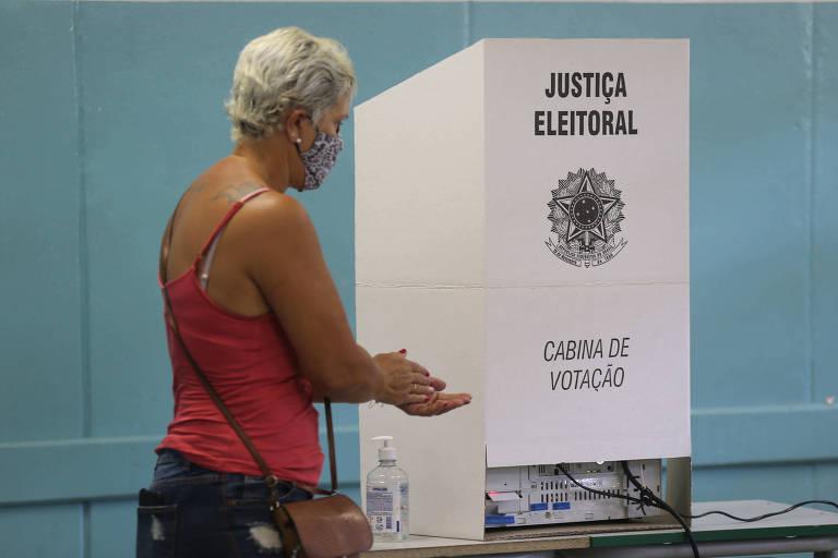 Mulher de regata de alcinha laranja, cabelo curto grisalho e bolsa lateral passa álcool em gel nas mãos perto de cabine de voto. Ao fundo, parede azul.