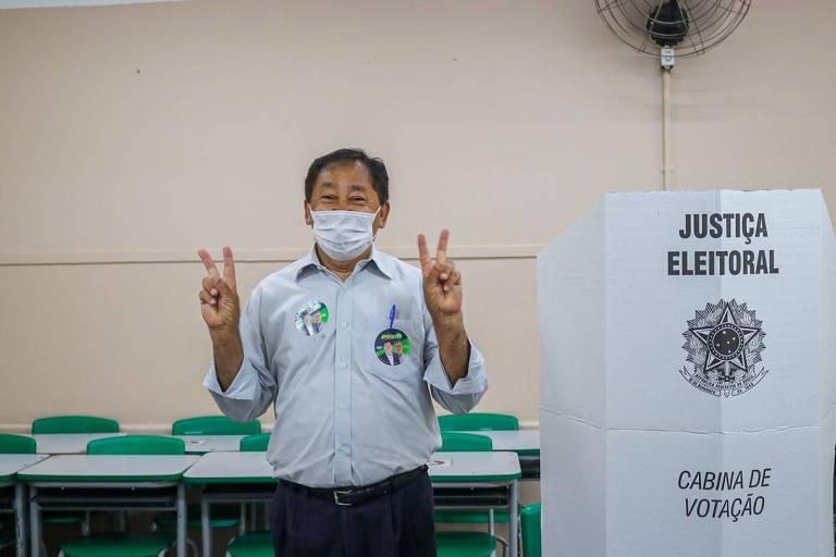 Aprigio fazendo sinal de vitória ao lado da cabine de votacao