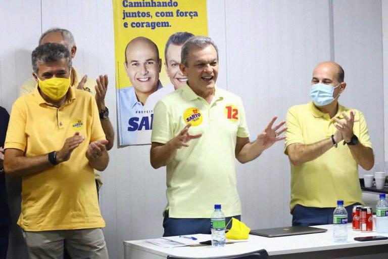 Três homens vestindo camisa polo amarela em diferentes tons estão atrás de mesa com um cartaz do candidato Sarto ao fundo. O homem no meio é José Sarto, do PDT, eleito prefeito de Fortaleza