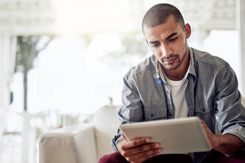 Shot of a young man using a digital tablet while sitting on the sofa in his living room
