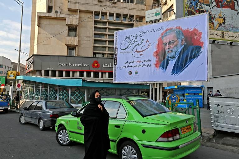 Mulher de burca em frente a um outdoor com a foto do cientista nuclear iraniano Mohsen Fakhrizadeh