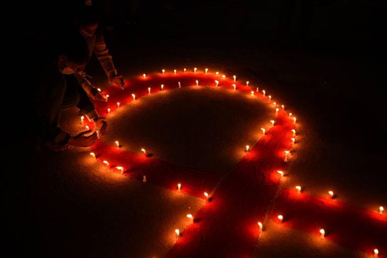 Imagem escura é iluminada por velas vermelhas, que formam um laço