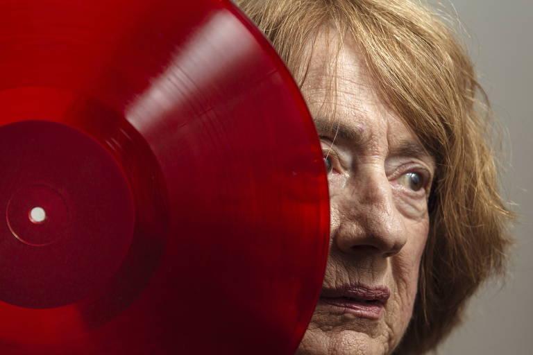 compositora jocy de oliveira atrás de um disco vermelho