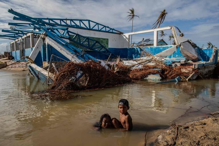 Crianças brincam em frente a uma casa destruída em Haulover, na Nicarágua, após a passagem do furacão Iota