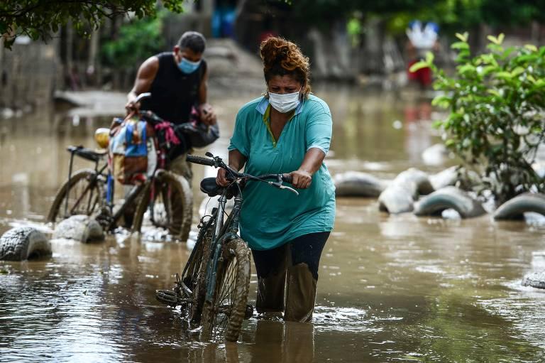 O hondurenho Guillermo Gomez atravessa área alagada pelo furacão Iota com a mulher, Blanca Calderón, e o filho Guillermo, na cidade de La Lima