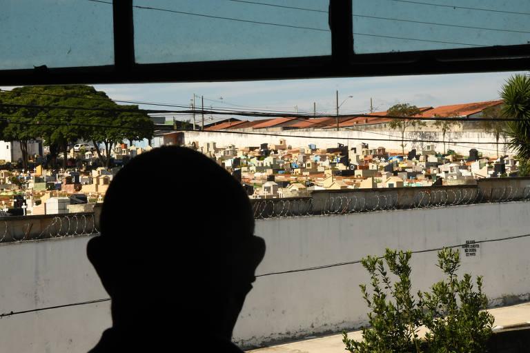 Reinaldo Moraes, 53, diante de janela de casa onde se vê o cemitério da Saudade, em Mogi das Cruzes (SP), onde está enterrado Gabriel Rogério, 20, um dos mortos no baile funk de Paraisópolis há 1 ano