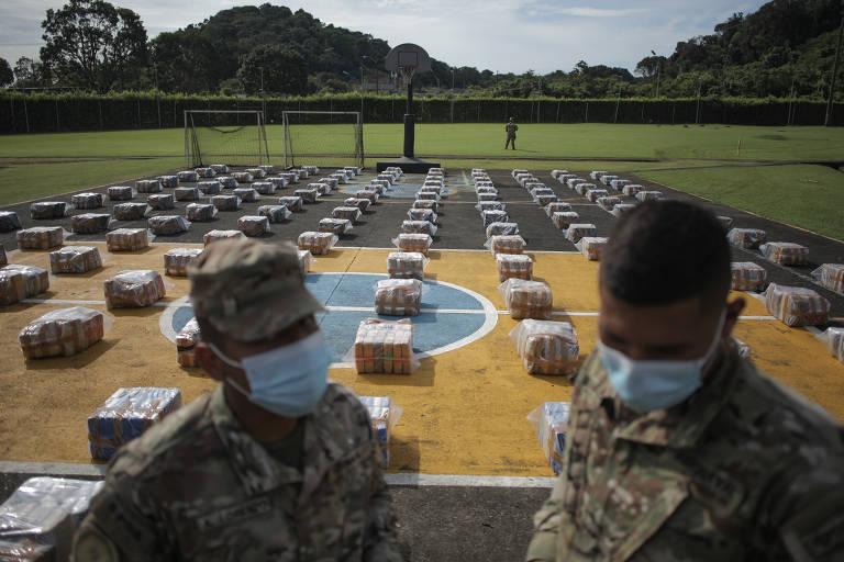 Dois homens fardados com dezenas de pacotes enfileirados em quadra poliesportiva ao fundo