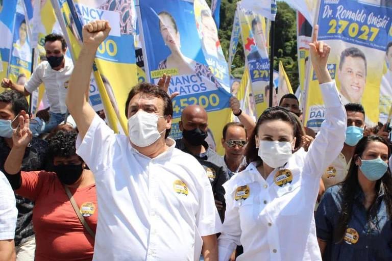 De mãos dadas, máscaras e braço erguidos, Fernandes e Analice caminham à frente de grupo com bandeiras com o rosto de Daniel