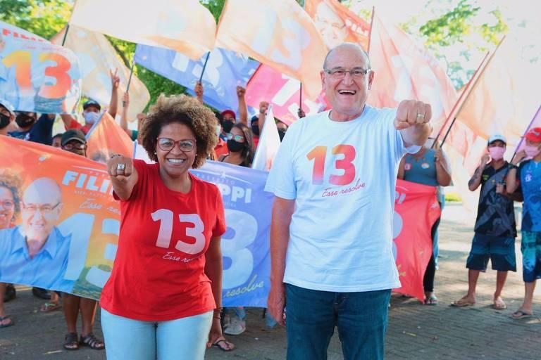 Vestidos com camisetas com o número 13, Patty, uma mulher negra, e Filippi, um homem branco mais velho, fazem gestos diante de militantes com bandeiras do candidato