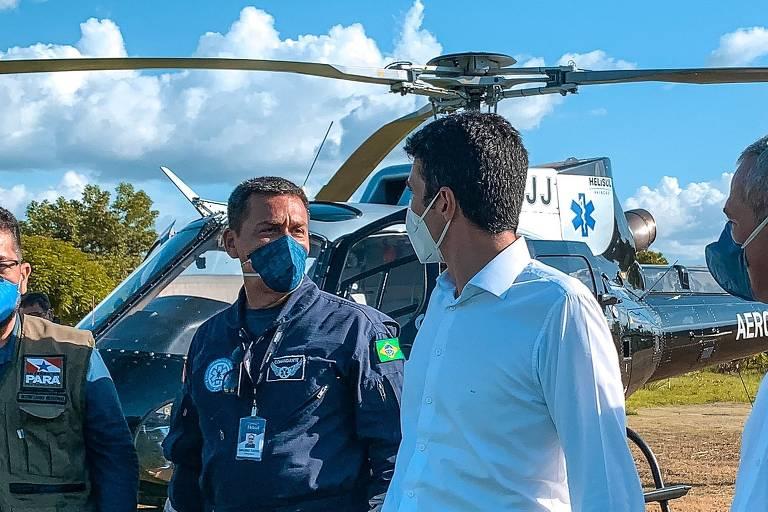 Dois homens de máscara, lado a lado; ao fundo, um helicóptero