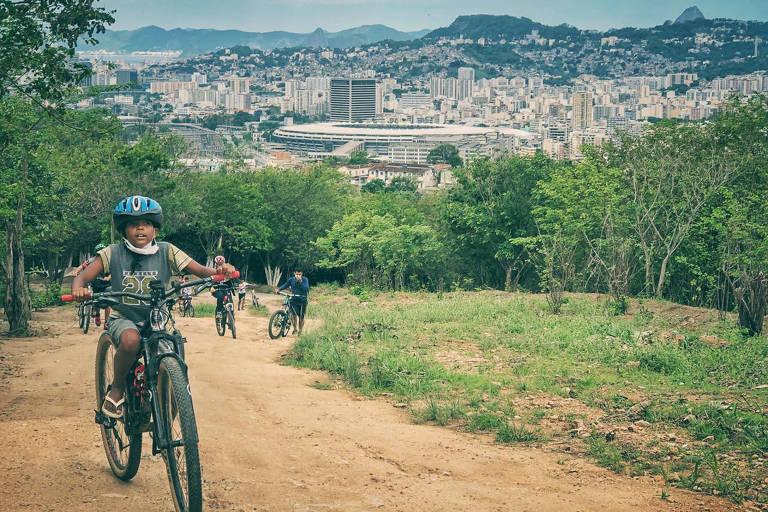 Crianças subindo ladeira de terra em bicicletas; é uma área que tem vegetação dos lados e, ao fundo, veem-se a cidade e morros