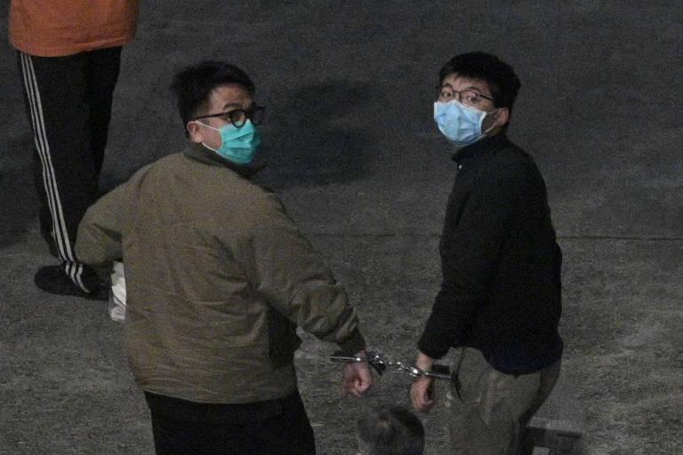 Imagem  mostra os ativistas pró-democracia em Hong Kong, Joshua Wong e Ivan Lam, presos com uma algema e usando máscaras, após serem condenados por incitar protesto ilegal